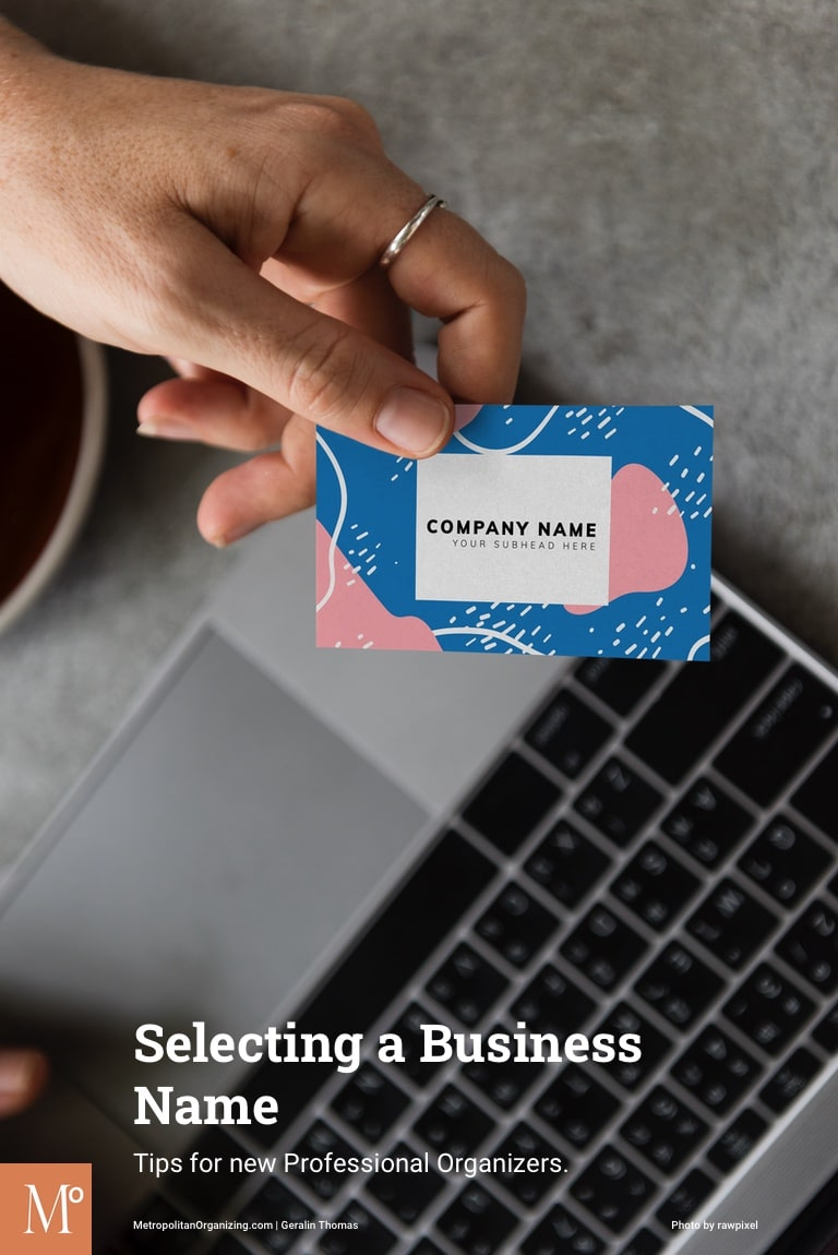 hand holding business card with no name on it above computer keyboard