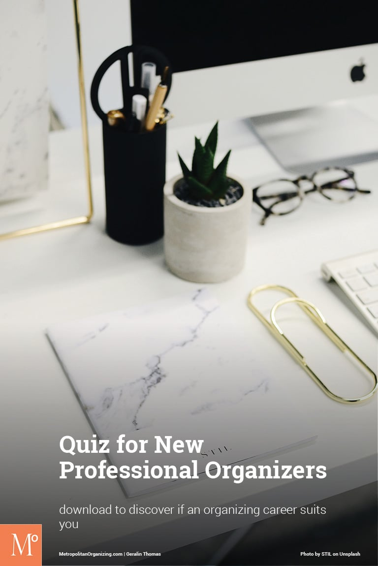 oversized gold paperclip on marble desk